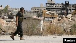 Một phiến quân đi bộ ngang qua những tòa nhà bị phá hủy ở Aleppo, Syria, ngày 16 tháng 9 năm 2016.