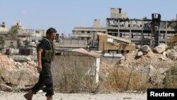 Một chiến binh của phiến quân đi ngang những tòa nhà bị hư hại gần Đường Castello ở Aleppo, Syria, ngày 16 tháng 9, 2016.