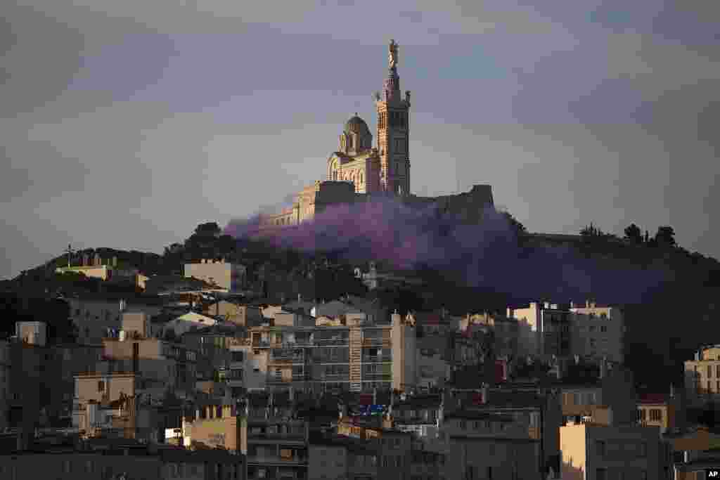 Stage technicians, theater administrators and actors set off smoke flares to demonstrate for more government support after the pandemic devastated their incomes, in front of the Notre-Dame de la Garde basilica in Marseille, southern France.