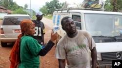 几内亚卫生工作者给人量体温。