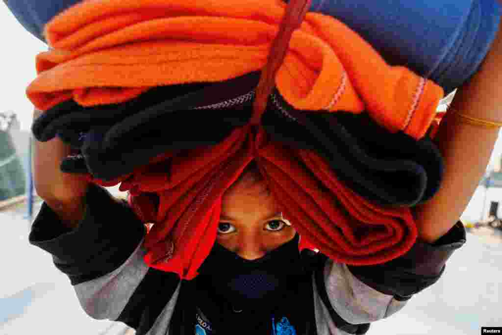A Rohingya girl carries blankets as she prepares to board a ship to move to Bhasan Char island near Chattogram, Bangladesh.