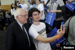 Democratic presidential candidate Bernie Sanders poses for a selfie with a supporter at a campaign rally at Iowa Wesleyan University in Mount Pleasant, Iowa, Jan. 29, 2016.