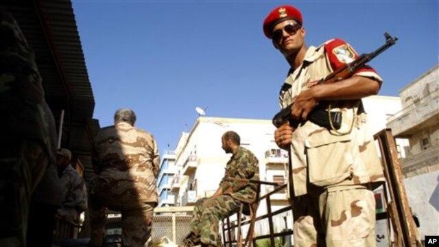 Pasukan keamanan Libya mengawasi penyerahan senjata dari warga sipil di Benghazi (29/9). Situasi di Benghazi masih terus rusuh dengan dibunuhnya kepala keamanan setempat.