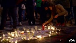 Brussels residents gather at the Place de la Bourse to light candles in memory of those killed in the terror attacks and sing songs of solidarity, March 22, 2016. (L. Bryant/VOA)