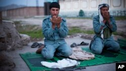 Afghan policemen pray at a checkpoint outside of Jalalabad, east of Kabul, in this March 18, 2013, file photo.