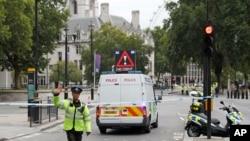 ایک پولیس اہلکار پارلیمان کی عمارت کی جانب جانے والی سڑک پر کھڑا ہے۔