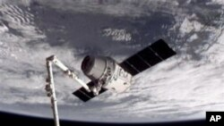 This image provided by NASA-TV shows the SpaceX Dragon commercial cargo craft, top, after Dragon was grappled by the Canadarm2 robotic arm and connected to the International Space Station, Friday, May 25, 2012. Dragon is scheduled to spend about a week do