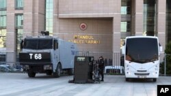 Security cars and an official stand outside the Justice Palace as a trial against Metin Topuz, a Turkish employee of the United States Consulate in Istanbul charged with espionage and attempting to overthrow the Turkish government, began in Istanbul, Marc