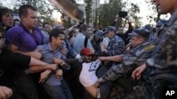 Police officers detain a protester in the opposition camp in Moscow