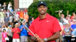 Tiger Woods holds Calamity Jane, the official trophy of the tournament, after winning the Tour Championship golf tournament, Sept. 23, 2018, in Atlanta.