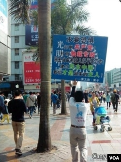 黄文勋举着一块足有一平方米大的标语牌走上了深圳人流熙攘的大街(2013年3月10日)