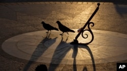 Birds are silhouetted next to the sundial in Sevastopol, Crimea, March 29, 2014.