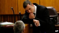 Oscar Pistorius berbicara dengan pengacaranya di sela sidang pengadilan di Pretoria, Afrika Selatan (16/10).