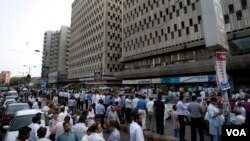Warga di kota Karachi, Pakistan keluar dari gedung setelah gempa yang berpusat di Iran terasa di Karachi (16/4).