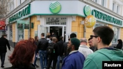FILE - People stand in a line as they wait to enter a branch of Sberbank of Russia bank in the Crimean city of Simferopol April 7, 2014.