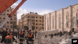 ພວກຄົນງານຊີເຣຍ ສຳຫຼວດເບິ່ງຄວາມເສຍຫາຍ ຢູ່ບ່ອນເກີດລະເບີດ ນອກຕຶກອາຄານສືບລັບທະຫານ ທີ່ເມືອງ Aleppo ໃນພາກເໜືອຊີເຣຍ (10 ກຸມພາ 2010)
