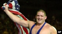 Rulon Gardner waves the American flag following his gold medal win against three-time Olympic gold medalist Alexandre Kareline, of Russia, in the Greco-Roman 130 kg final wrestling match at the XXVII Summer Games in Sydney, 27 Sep 2000 (file photo)