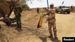 A fighter with the Tuareg separatist group MNLA (National Movement for the Liberation of Azawad) brandishes a separatist flag for the region they call Azawad outside the local regional assembly, where MNLA members met with the Malian army, the U.N. missio