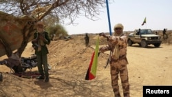 FILE - Fighter with Tuareg group MNLA brandishes separatist flag for region they call Azawad outside local regional assembly, Kidal, June 23, 2013.