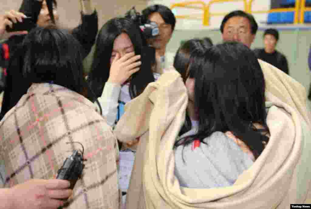 16일 한국 전남 진도 해상에서 침몰한 여객선에 탑승객 중 구조된 학생들이 진도군 실내체육관에서 서로를 확인한 후 울음을 터뜨리고 있다.