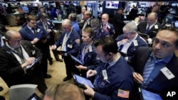 Traders gather at a post on the floor of the New York Stock Exchange, Feb. 26, 2016.
