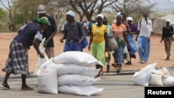Zimbabweans collect food aid from a distribution point in Mutawatawa, about 220km northeast of the capital Harare, November 25, 2013. According to the World Food Programme (WFP), over 2 million FILE: Zimbabwean people are in need of food aid due to a poor harvest. Picture taken November 25, 2013. REUTERS/Philimon Bulawayo (ZIMBABWE - Tags: POLITICS SOCIETY) - RTX15TGB