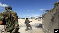 Anti-Gadhafi fighters return fire during clashes with pro-Gadhafi forces in the center of Sirte October 17, 2011.