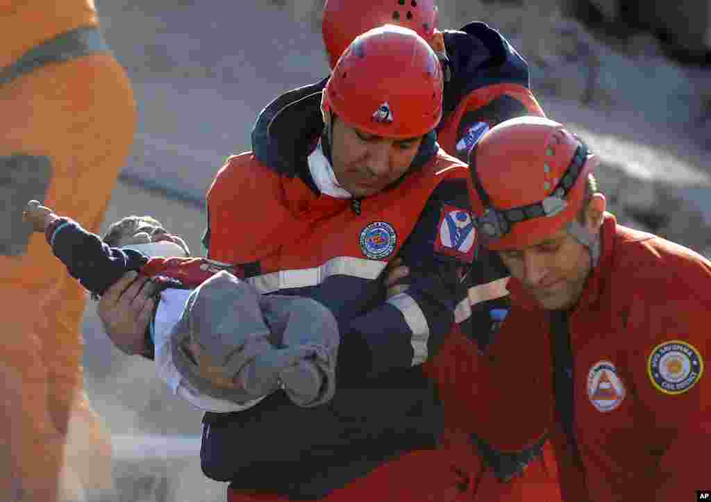 A rescue worker carries a boy to an ambulance after his team found him alive in a collapsed building in Ercis, near the eastern Turkish city of Van, October 24, 2011. (Reuters)