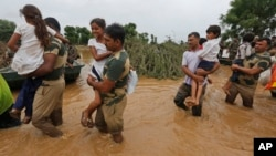 FILE - India army soldiers carry children rescued from flood affected villages near Thara in Banaskantha district, Gujarat, India, July 26, 2017.