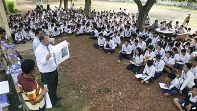 The officers of U.N.-backed genocide tribunal meet high school students at Ek Phnom district in Battambang province, as they distribute recent verdict books of Khmer Rouge leader Kaing Guek Eav, northwest of Phnom Penh, Cambodia, May 5, 2011