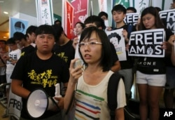 Singaporean protester Han Hui-hui, center, accompanied by Hong Kong students, speaks during a protest outside the Singapore Consulate in Hong Kong, June 30, 2015, to urge Singapore's government to release teen blogger Amos Yee. Yee had been found guilty of insulting Christians in a video monologue, and of distributing an obscene image of the country's founding father, Lee Kuan Yew.