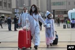 武汉解封,穿着防护服和口罩的人们到达武汉的汉口火车站。(2020年4月8日)