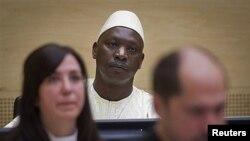 Thomas Lubanga mwenye kofia akiwa kwenye chumba cha mahakama na mawakili wake huko The Hague