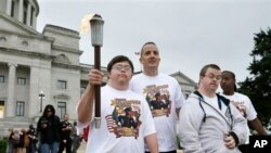 David Dallas, left, carries the Arkansas Special Olympics Torch accompanied by Little Rock police Capt. Heath Helton, center, and other athletes at the Arkansas state Capitol in Little Rock, Ark., May 21, 2015.