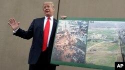 Tổng thống Donald Trump cầm một bức hình cho thấy khu vực biên giới khi ông tới thị sát các bức tường nguyên mẫu, ngày 13 tháng 3, 2018, ở San Diego, California.
