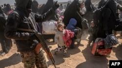 Perempuan dan anak-anak dievakuasi dari wilayah pertahanan kelompok militan ISIS di Baghuz tiba di daerah pemeriksaan yang dikuasai oleh Pasukan Demokratik Suriah yang didukung AS di Deir el-Zour, provinsi di sebelah timur Suriah, 6 Maret 2019.