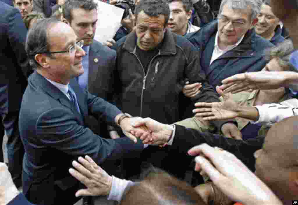 President-elect Francois Hollande shakes hand with supporters as he leaves his campaign headquarters in Paris, Wednesday May 9, 2012. After winning the French Presidential Election, Hollande seems set to embark on a whirl-wind introduction to internation