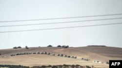 This picture taken from the Turkish Syrian border city of Karkamis in the southern region of Gaziantep, on Aug. 24, 2016 shows Turkish army tanks and pro-Ankara Syrian opposition fighters moving two kilometres west from the Syrian Turkish border town of J