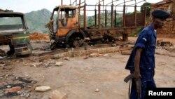 Un policier congolais assure la sécurité près des épaves de camions vandalisés au siège de mouvement politico-religieux Bundu Dia Kongo, à Matadi, Kongo central, 19 mars 2008.