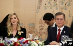 In this photo provided by South Korea Presidential Blue House, Ivanka Trump, the daughter of U.S. President Donald Trump, and South Korean President Moon Jae-in, right, attend a dinner at the presidential Blue House in Seoul, South Korea, Feb. 23, 2018.