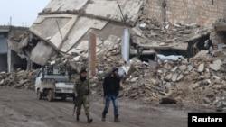 30일 시리아 알레포 외곽 알-라이 마을에서 반군 병사들이 무너진 건물터를 지나고 있다.