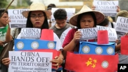 Filipino student activists hold mock Chinese ships to protest recent island-building and alleged militarization by China off the disputed Spratlys group of islands in the South China Sea during a rally near the Malacanang presidential palace in Manila, Ph