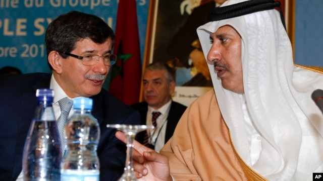 Turkish Foreign Minister Ahmet Davutoglu, left, chats with Qatar's Prime Minister and Foreign Minister Sheik Hamad bin Jassim al-Thani at a meeting of the Friends of the Syrian People in Marrakech, Morocco, Wednesday, Dec. 12, 2012.