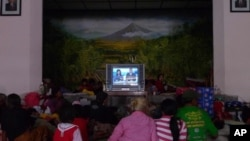 Evacuees gather to watch television to stave off boredom at the Wonokerto evacuation shelter
