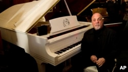 FILE - Billy Joel poses at a piano in New York, Dec. 12, 2011.