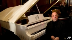 Billy Joel poses et son piano à New York (Photo AP)