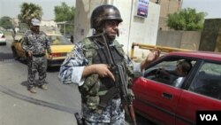 Polisi Irak berjaga-jaga setelah terjadinya ledakan di perbatasan Baghdad hari ini.
