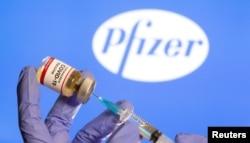 """Seorang perempuan memegang botol kecil berlabel """"Vaksin Coronavirus COVID-19"""". (Foto: Reuters)"""