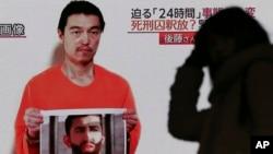 Siaran televisi di Jepang menayangkan sosok Kenji Goto yang disandera ISIS tengah memegang foto pilot Yordania Mu'ath al-Kaseasbeh di Tokyo (28/1).