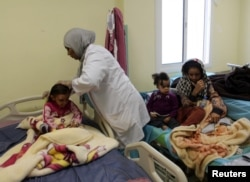 FILE - Children, who Libyan forces said left the last cluster of buildings controlled by Islamic State in the group's former stronghold of Sirte, receive medical treatment in a hospital in Misrata, Libya, Dec. 4, 2016.
